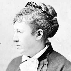 A middle aged women, photographed in profile. Her hair is in a bun.