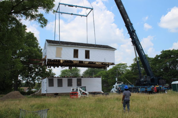 A crane lifts the second story off the a white clapboard two story house.